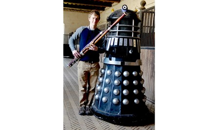 A photograph of Oliver Ludlow, Director and Bassoon Specialist at Double Reed Ltd., standing with an authentic BBC 'Dalek' from the TV show 'Dr Who'