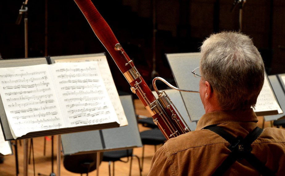 Person playing bassoon in an orchestral setting